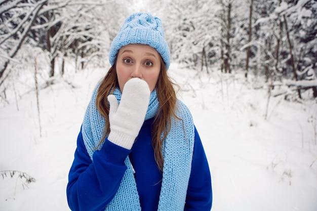 青いトラックスーツの白いミトンとスカーフの女性が立って、雪に覆われた森の中で冬に驚きます