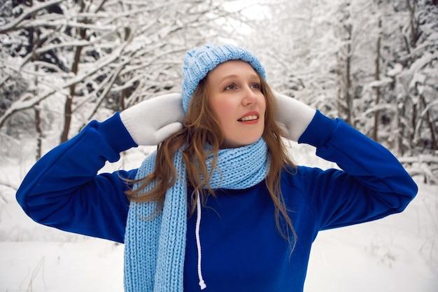 파란색 tracksuit 흰 장갑과 스카프에 여자는 눈이 덮여 숲에서 겨울에 서