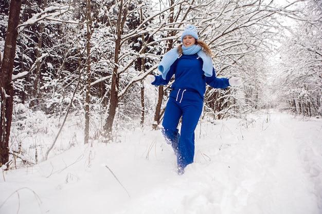青いトラックスーツの白いミトンとスカーフの女性は、雪に覆われた森の冬に立っています