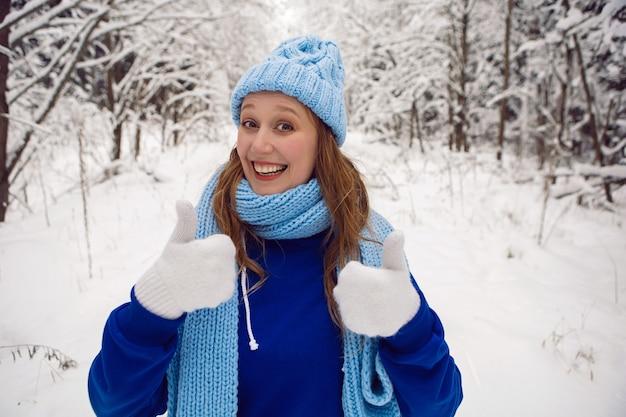 青いトラックスーツの白いミトンとスカーフの女性は、雪に覆われた森の中で冬に親指を立てます