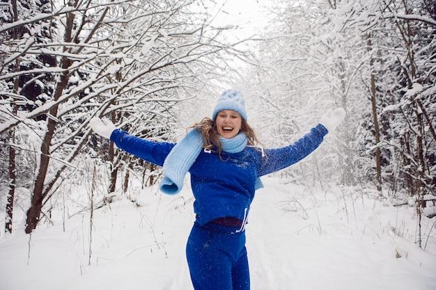 雪に覆われた森で冬に雪を投げるために青いトラックスーツの白いミトンとスカーフの女性