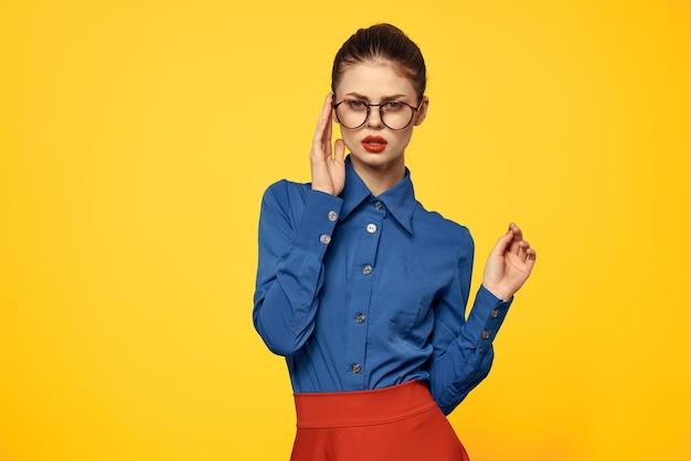 Женщина в ярко-синей рубашке и красной юбке позирует