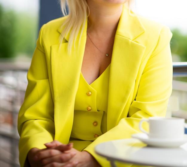 Женщина в ярко-желтом деловом костюме за столиком в летнем кафе, до неузнаваемости