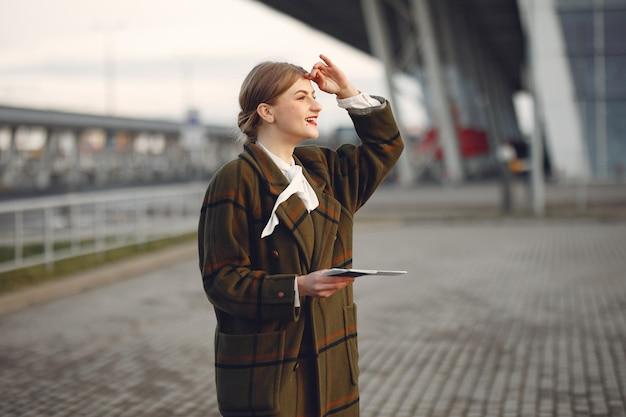 空港のそばに立っている茶色のコートを着た女性