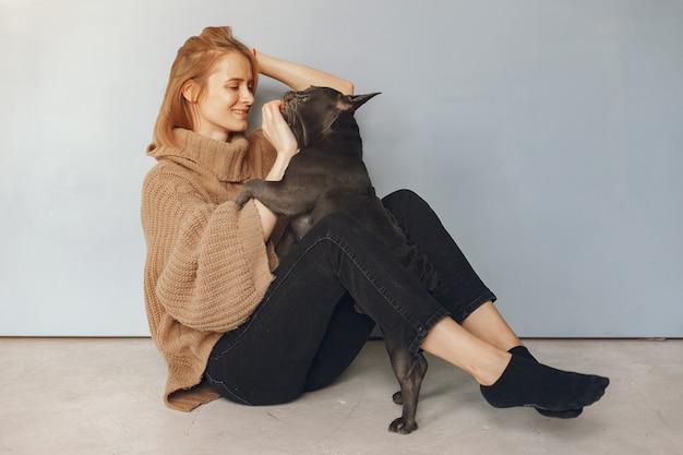 Женщина в коричневом свитере с черным бульдогом