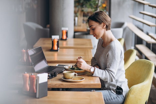 Женщина в кафе с обедом и разговаривает по телефону