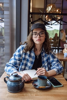 카페에 있는 여자는 공책에 글을 쓰고 카메라를 본다