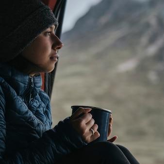 一杯のコーヒーとキャンピングカーの女性