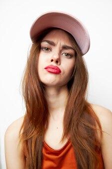 帽子をかぶった女性生意気なグラマーモデルの赤いサンドレス