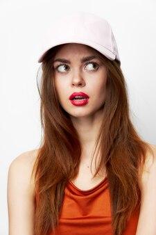 帽子をかぶった女性が口を開けて横向きに見えるクロップドビュー