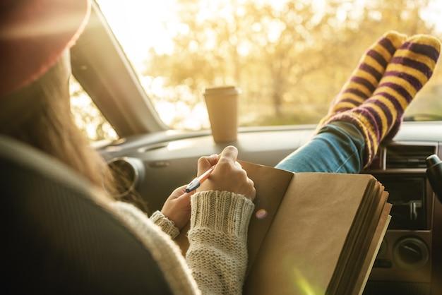 Женщина в машине в теплых носках пишет заметки и планы в блокноте