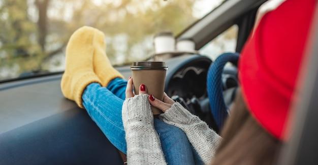 暖かいウールの黄色い靴下を履いた車の中で女性が手にコーヒーを持っています