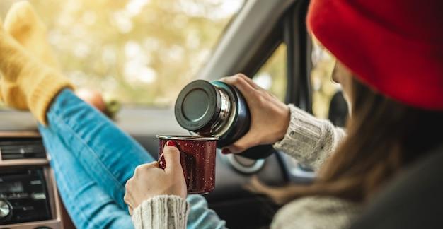 暖かいウールの黄色い靴下を履いた車の女性が魔法瓶からカップにコーヒーを注いでいます。居心地の良い秋の週末旅行