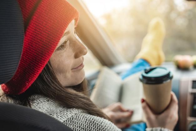 暖かいウールの黄色い靴下を履いた車の中で女性が助手席に座って本を読んでいます
