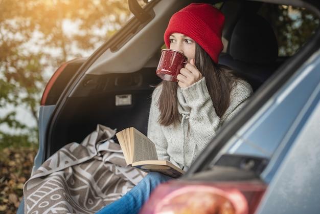 Женщина в машине в теплых шерстяных желтых носках читает книгу, сидя в багажнике машины на пикнике