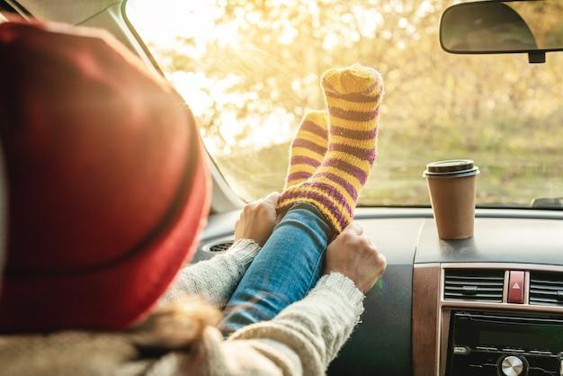Женщина в машине в теплых шерстяных желтых носках на приборной панели автомобиля