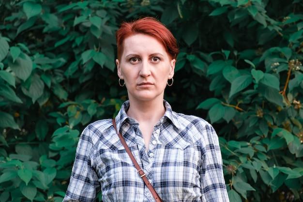 茂みの緑の葉を背景に、市松模様のシャツを着た女性が立っています。
