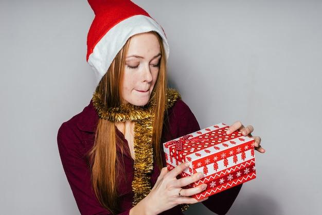 クリスマスの帽子をかぶった女性は彼女の手に贈り物を持っています