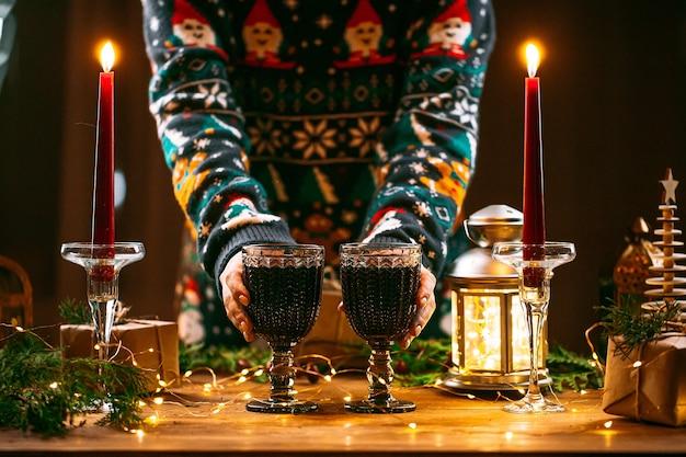 グリントワインのマグカップを保持しているクリスマスセーターの女性