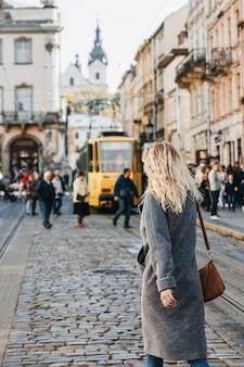 コートを着た女性がリヴィウの旧市街中心部にあるリノック広場の通りを歩いています。