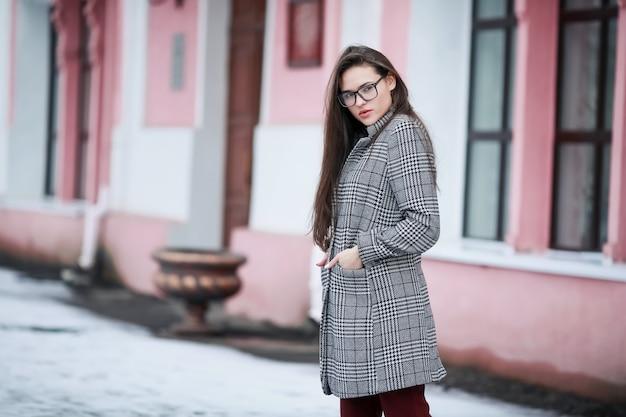 都市の背景にコートを着た女性