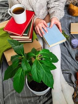 Женщина в уютной домашней атмосфере пьет чай и читает книги