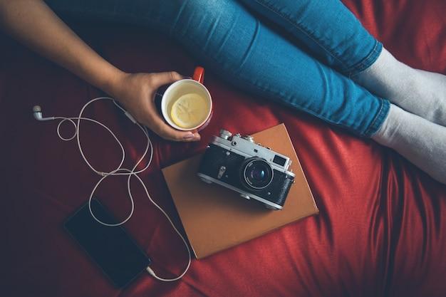 古い本と彼らの手で牛乳と紅茶のカップが付いているベッドの上の居心地の良いセーターの女性トップビュー