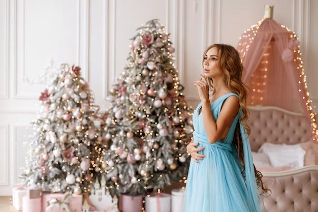 침실에있는 크리스마스 트리에서 화장과 섬세한 드레스 여자
