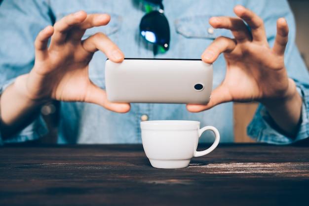 Женщина в джинсовой рубашке фотографирует чашку кофе в кафе