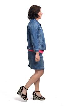 Женщина в джинсовой юбке и куртке, ходить на белом фоне