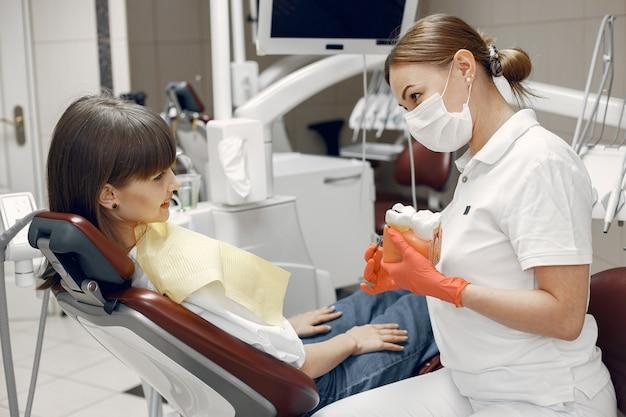 치과 의자에 여자입니다. 치과 의사는 적절한 관리를 가르치고 미용은 치아를 치료합니다.