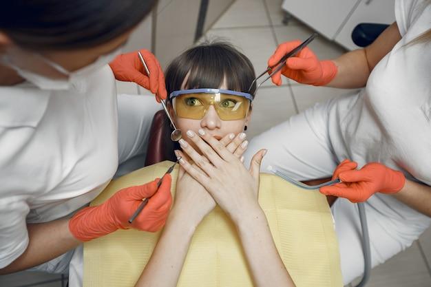 치과 의자에 여자입니다. 소녀는 입을 가리고 치과 의사는 소녀의 치아를 치료합니다.