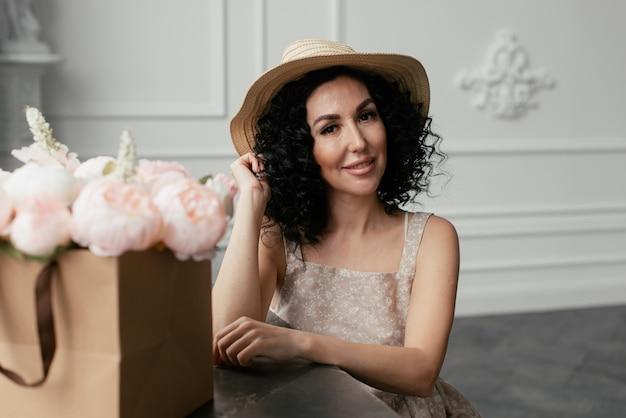花の花束の横にあるドレスと麦わら帽子の女性