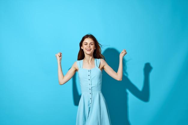 ドレスとメガネの青い背景のライフスタイルの女性。高品質の写真