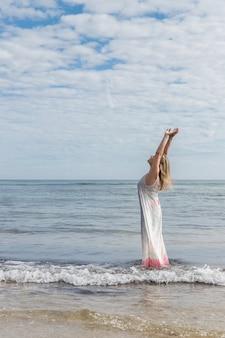 腕を上げて自由を楽しむ海のドレスを着た女性