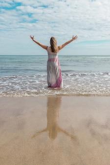 両手を広げて彼女の自由を楽しんでいる海のドレスを着た女性