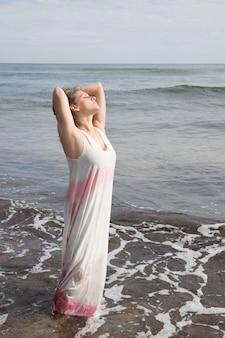 彼女の自由を楽しんでいる海のドレスを着た女性