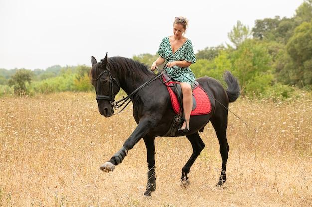 自然の中で馬に乗ってドレスを着た女性