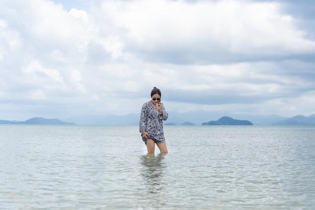 Женщина в платье стоит в морской воде и разговаривает по мобильному телефону.