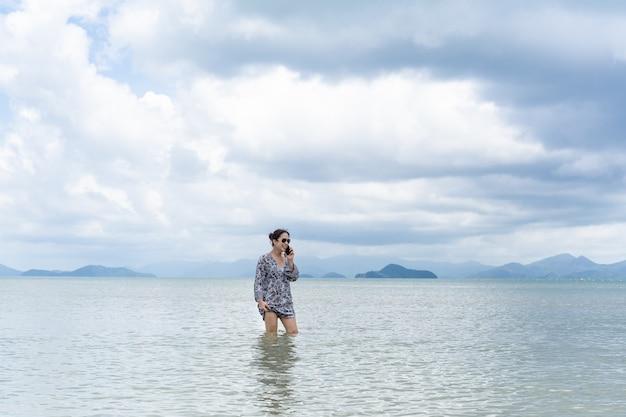 海の水に立って携帯電話で話しているドレスを着た女性。