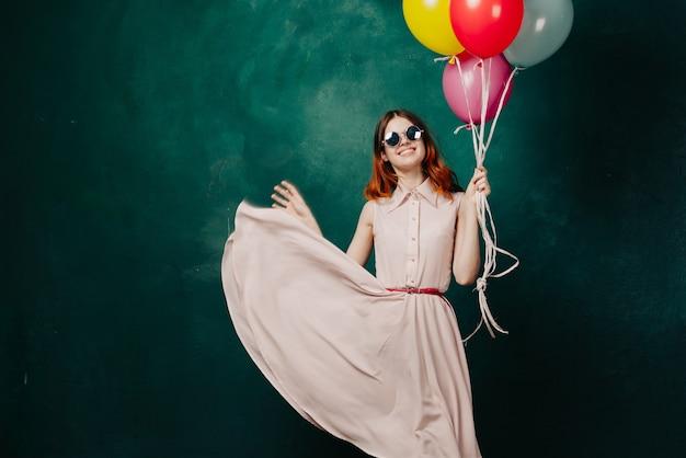 Женщина в платье с воздушными шарами в руке