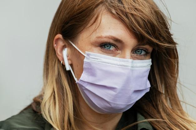 코로나바이러스 전염병 동안 음악을 듣는 마스크를 쓴 여성