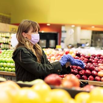 コロナウイルス検疫中にスーパーマーケットで買い物中にラテックス手袋を着用したフェイスマスクの女性