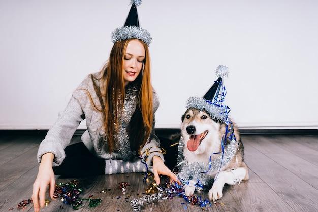 Женщина в праздничной шляпе сидит на полу рядом друг с другом