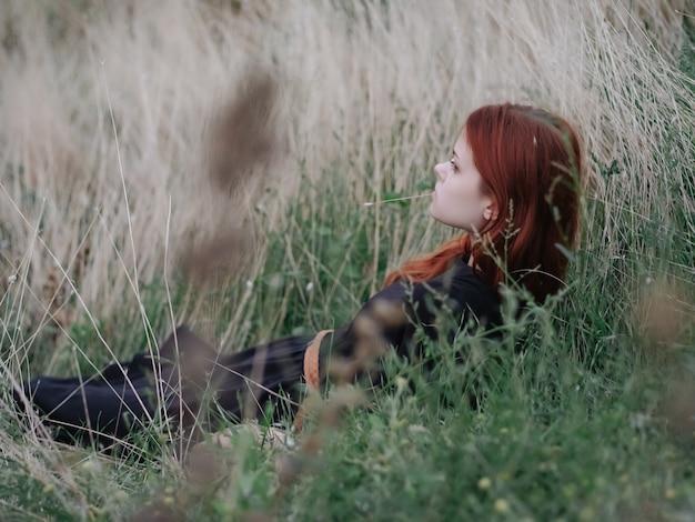 自然の中でフィールドにいる女性は芝生の上に横たわっています