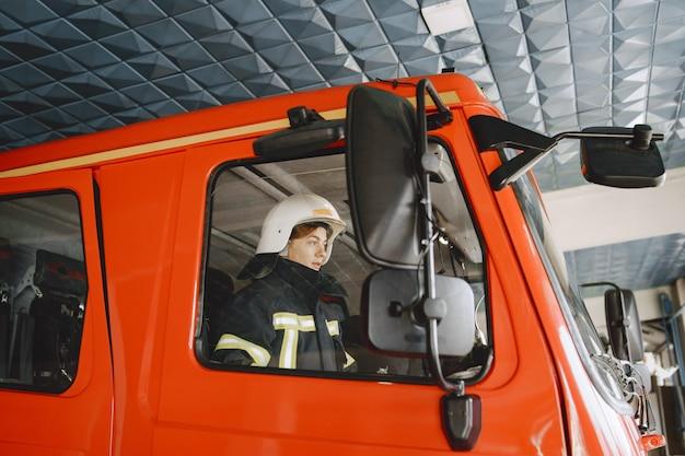 消防車の女性。赤い消防車。消防士は車のドアを閉めます。