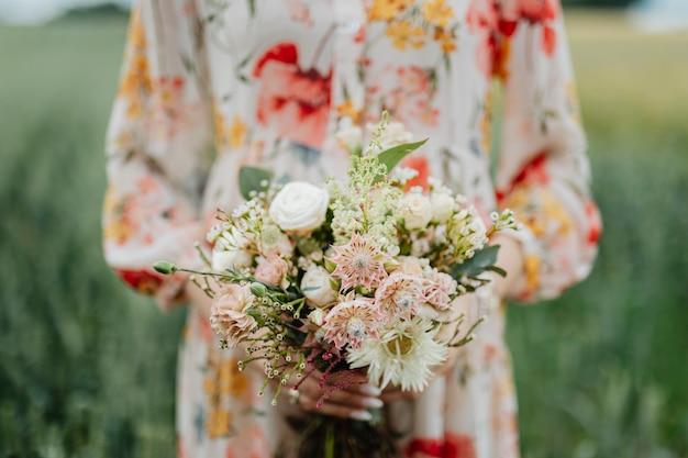 花の花束を持っている花柄のドレスを着た女性