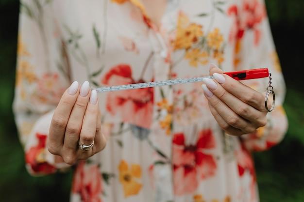 測定テープを保持している花柄のドレスを着た女性