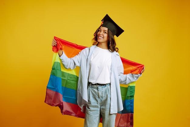 Женщина в выпускной шляпе позирует с радужным флагом лгбт на желтом