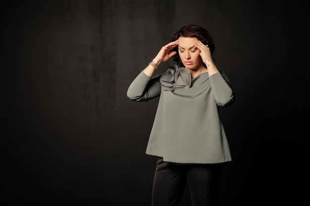 Женщина в серой блузке с головной болью, головокружением, прикосновением к вискам, закрывая глаза
